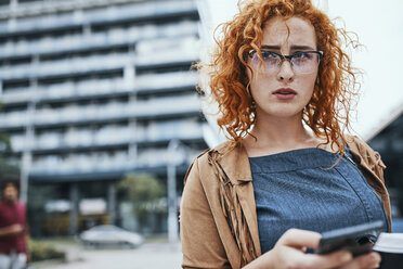 Young woman walking in the city, using smartphone - ZEDF01515