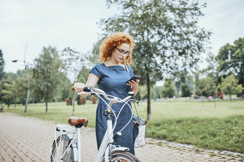 Young woman walking in park, pushing bicycle - ZEDF01536