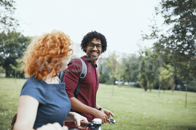 Friends walking in park, talking, woman pushing bicycle - ZEDF01539