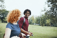 Friends walking in park, talking, woman pushing bicycle - ZEDF01539
