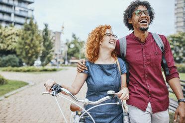 Friends walking in park, talking, woman pushing bicycle - ZEDF01542