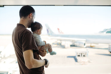 Man holding a baby girl at the airport, looking at the airplanes - GEMF02400