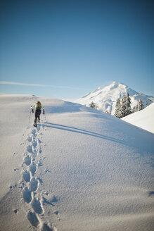 A snowshoer walks a snow covered ridgeline. - AURF03737