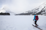 A woman  skiing on Two Medicine Lake in front of Sinopah Mountain in Glacier National Park, Montana. - AURF03800