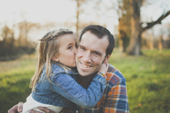 A young girl kisses her dad on the cheek. - AURF03827