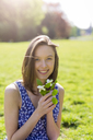 Portrait of smiling young woman in a park holding flowers - GIOF04280