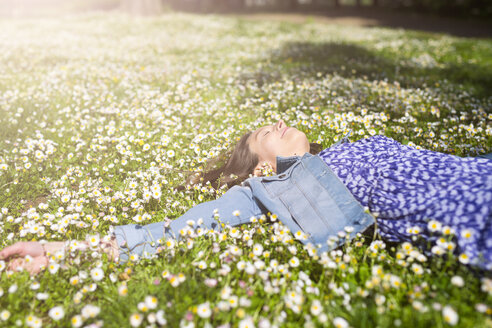 Relaxed young woman lying on flower meadow in a park - GIOF04283