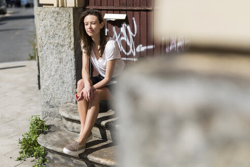 Smiling young woman sitting on stairs in the city - GIOF04292