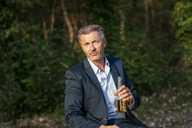 Portrait of businessman with beverage in nature - FMKF05214