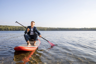 Businessman paddling on lake - FMKF05223