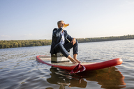 Businessman sitting on surfboard on a lake having a drink - FMKF05226