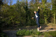 Businessman balancing barefoot on pole in nature - FMKF05229