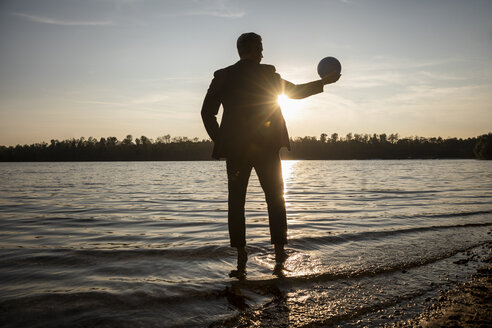 Silhouette of businessman standing at lakeshore by sunset looking at ball in his hand - FMKF05232