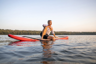 Man sitting on paddleboard on a lake by sunset relaxing - FMKF05241