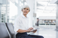 Senior businesswoman sitting in waiting area with tablet looking around - DIGF05019