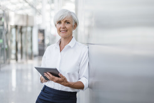 Portrait of smiling senior businesswoman holding tablet - DIGF05022