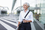 Smiling senior businesswoman in the city on the go - DIGF05028