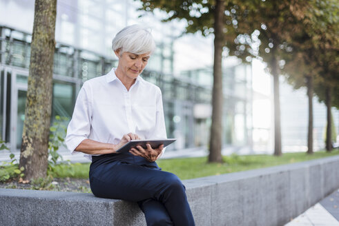 Senior businesswoman sitting outside using tablet - DIGF05037