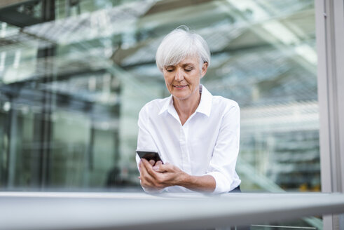 Senior businesswoman leaning on railing in the city looking at cell phone - DIGF05046