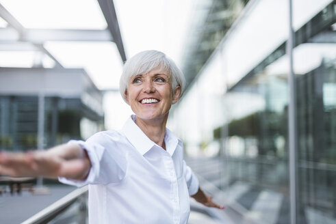 Happy senior woman in the city with outstretched arms - DIGF05049