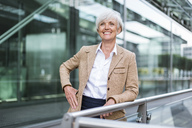 Portrait of smiling senior businesswoman leaning on railing in the city - DIGF05052