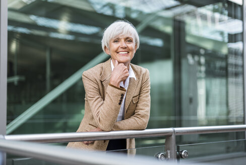 Portrait of smiling senior businesswoman leaning on railing in the city - DIGF05055