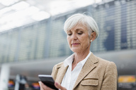 Senior businesswoman using cell phone at the airport - DIGF05064