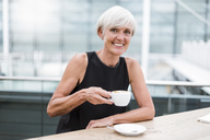 Portrait of smiling senior woman drinking a coffee - DIGF05076