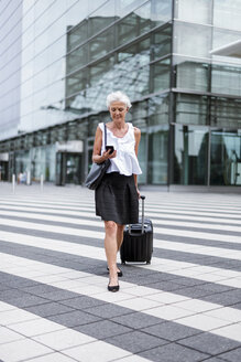 Smiling senior woman with baggage on the move looking on cell phone - DIGF05088