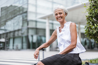 Portrait of happy senior woman with baggage sitting in the city - DIGF05091