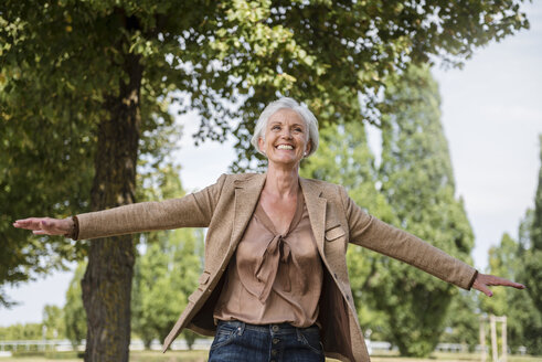 Happy senior woman with outstretched arms in a park - DIGF05112