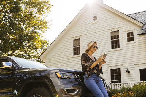 Smiling young woman using mobile phone while leaning on car outside house - TGBF00032