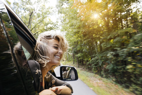 Beautiful young woman looking out of car window during road trip in countryside - TGBF00035