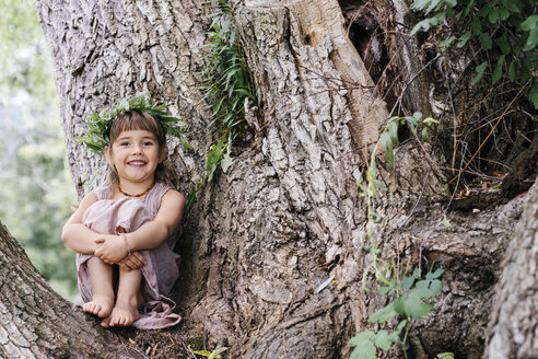 Portrait of cheerful girl wearing a crown while sitting in tree - TGBF00068