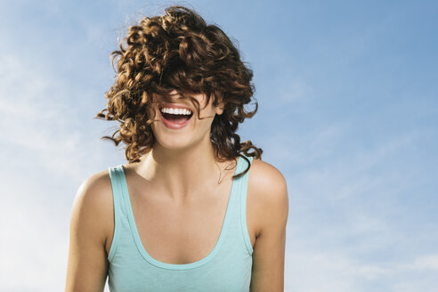 Cheerful young woman with tousled curly hair standing against blue sky - TGBF00095