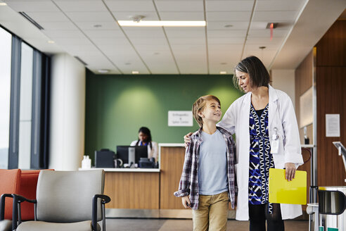 Smiling mature female doctor talking to boy while walking with him in hospital corridor - TGBF00221