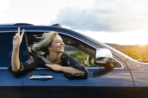 Smiling young woman gesturing peace sign while looking out of car window during road trip - TGBF00233