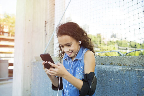 Smiling girl with elbow pads and headphones listening music through smart phone in city - TGBF00245
