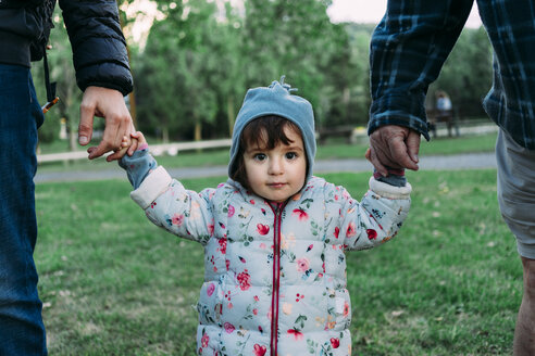 Portrait of fashionable little girl walking through a park on grandfather's and father's hands - GEMF02407