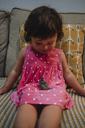 Smiling little girl sitting on the couch with sparrow on lap - GEMF02416