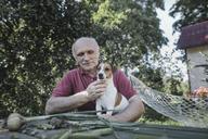 Senior man sitting with dog at garden table - KMKF00529