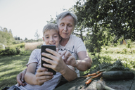 Grandmother and grandson taking a selfie in garden - KMKF00532
