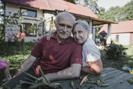 Portrait of senior couple sitting at garden table - KMKF00535