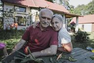 Portrait of senior couple sitting at garden table - KMKF00535