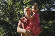 Grandfather carrying granddaughter in garden - KMKF00538