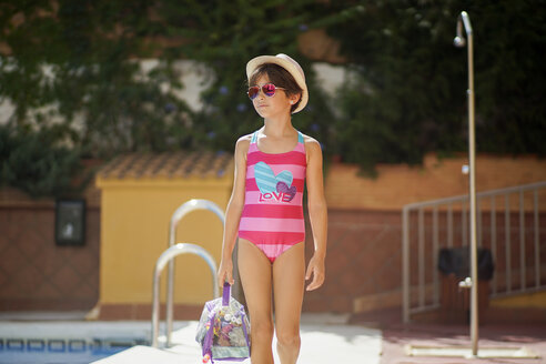 Young girl arriving at the pool in summer with bath clothes - JSMF00437