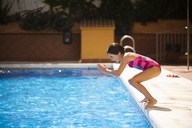 Young girl jumping head first into the pool in summer - JSMF00446