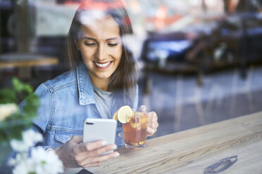 Smiling young woman using phone and drinking tea in cafe - BSZF00566