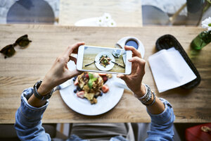 Overhead view of woman taking smartphone picture of pancakes in cafe - BSZF00575