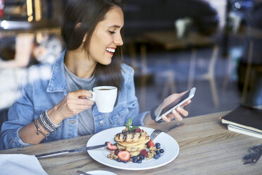 Smiling young woman with plate of pancakes using phone in cafe - BSZF00578